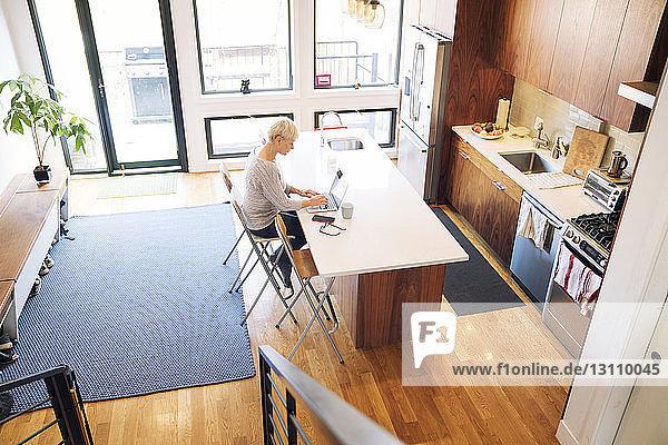 Hochwinkelansicht einer älteren Frau mit Laptop am Küchentisch zu Hause