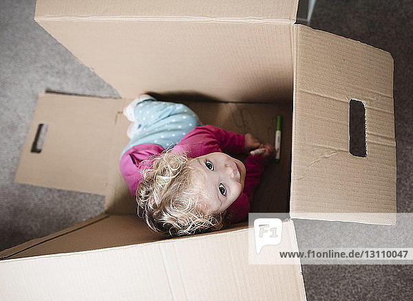 High angle view of playful girl sitting in cardboard box at home