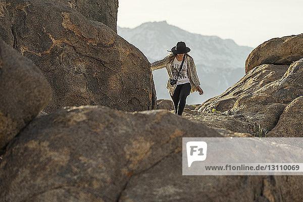 Junge Frau wandert auf Berg gegen Himmel