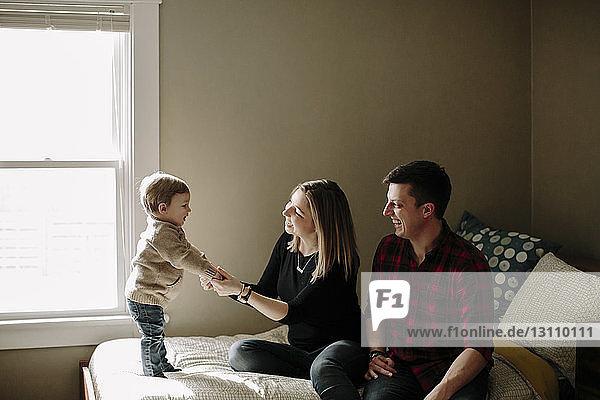 Glückliche Eltern spielen mit ihrem Sohn zu Hause im Bett