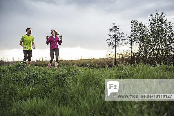 Glückliche Freunde unterhalten sich beim Joggen auf einem Grasfeld