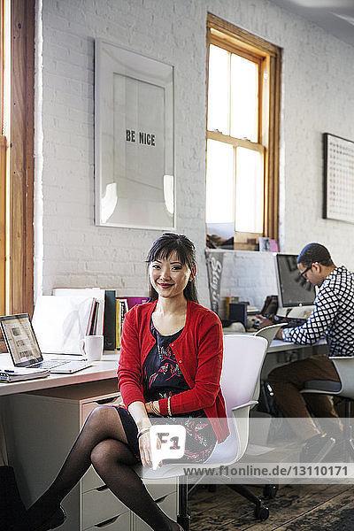 Porträt einer lächelnden Geschäftsfrau  die im Büro sitzt
