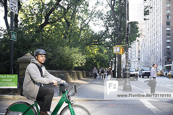Man looking away while riding bicycle on city street