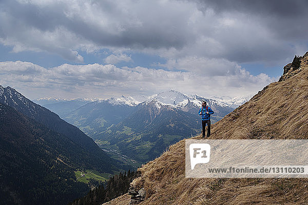 Thoughtful male hiker standing on mountain against cloudy sky