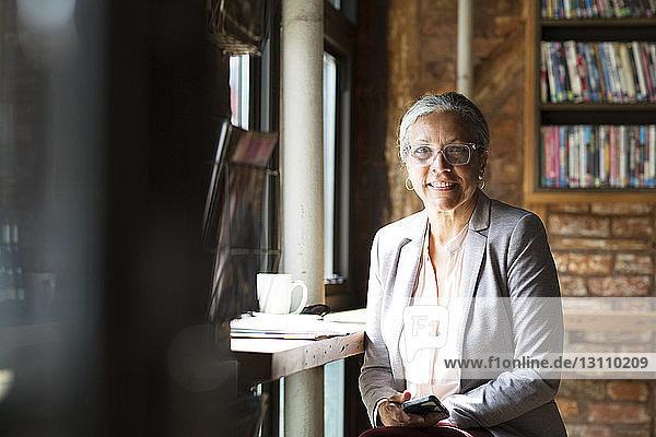 Porträt einer lächelnden Frau beim Kaffeetrinken in einem Café