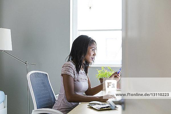 Woman working at home office seen through doorway