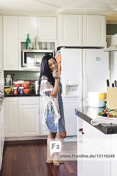 Ganzfigur einer lächelnden Frau  die in der Küche auf einem Hartholzboden stehend Essen isst