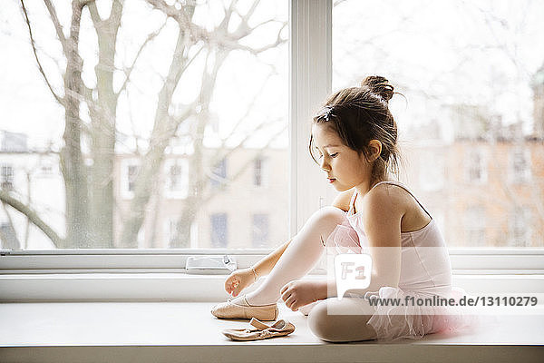 Close-up of girl wearing ballet shoes while sitting on window