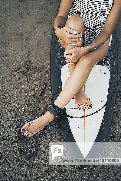 Low section of woman sitting on surfboard at beach
