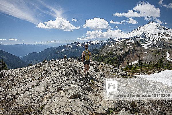 Rückansicht einer Wanderin  die im Winter im North Cascades National Park auf Felsformationen vor Bergen und bewölktem Himmel wandert