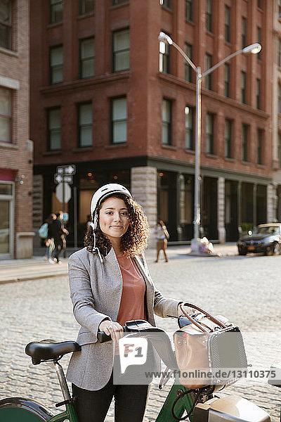 Porträt einer Geschäftsfrau  die eine Fahrradaktie auf einem Parkplatz auf der Straße hält