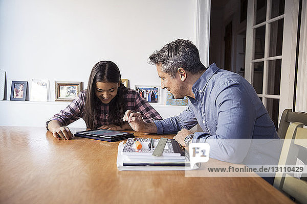 Father and daughter using tablet computer while sitting at table