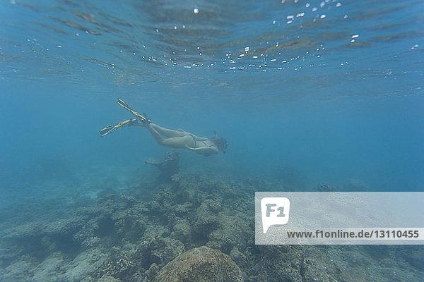 Frau trägt Bikini beim Schwimmen im Meer