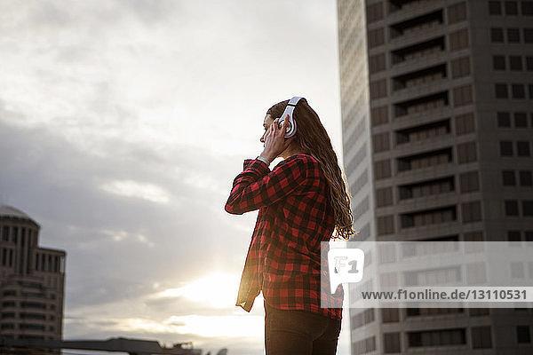 Seitenansicht einer Frau  die Kopfhörer trägt  während sie an Gebäuden steht