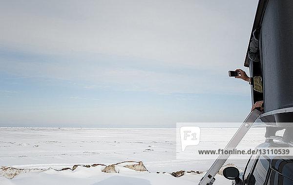 Ausgeschnittene Hände einer Frau  die im Winter vom Dachzelt aus auf einem Auto fotografiert