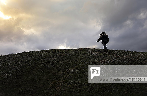 Low angle view of carefree girl climbing hill against cloudy sky