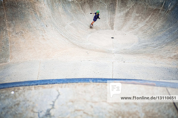 High angle view of girl skateboarding on sports ramp in park