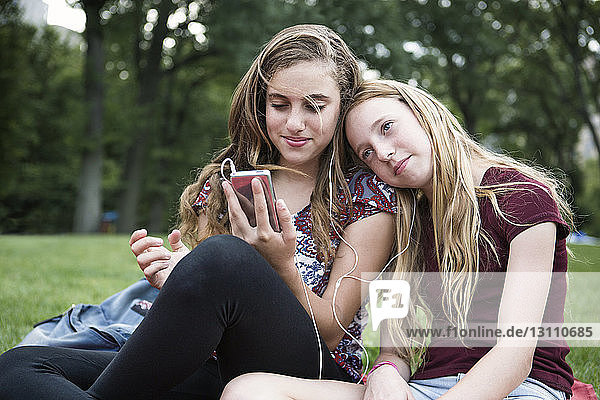 Smiling sisters listening music while relaxing on grassy field at park