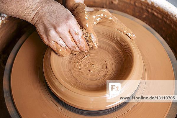 Hochwinkelansicht von Frauenhänden beim Formen von Ton auf der Töpferscheibe