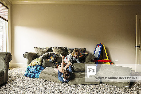 Boys playing with couch cushions at home