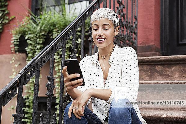 Glückliche Frau benutzt Mobiltelefon  während sie auf einer Treppe sitzt
