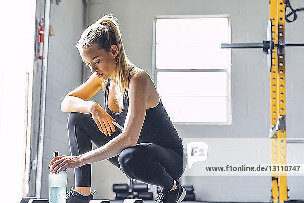 Müde Frau hält Wasserflasche in der Hand,  während sie im Fitnessstudio kauert