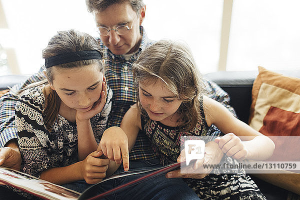 Father with daughters looking at book while sitting on sofa at home