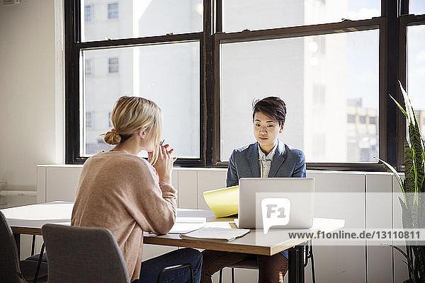 Weibliche Kollegen diskutieren am Schreibtisch im Büro