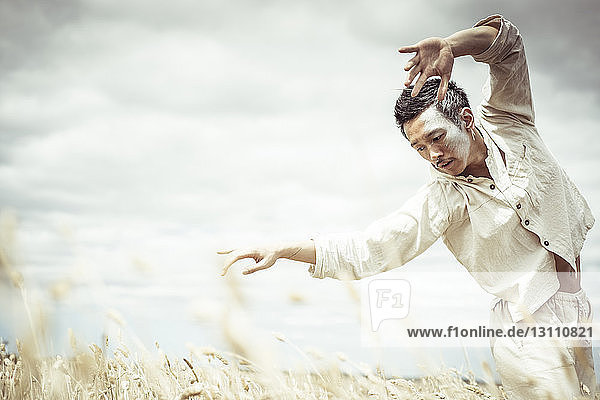 Man dancing on field against cloudy sky at farm during sunny day