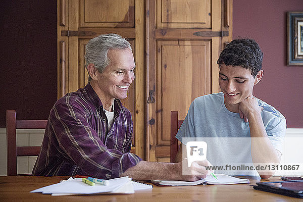 Grandfather assisting grandson while studying at table in home