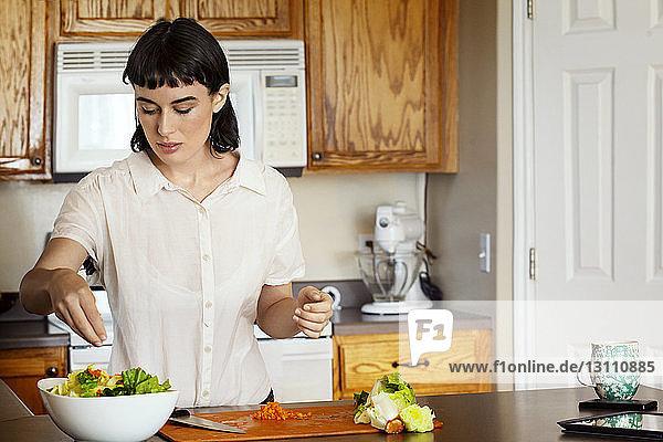Frau würzt Salat  während sie zu Hause in der Küche steht