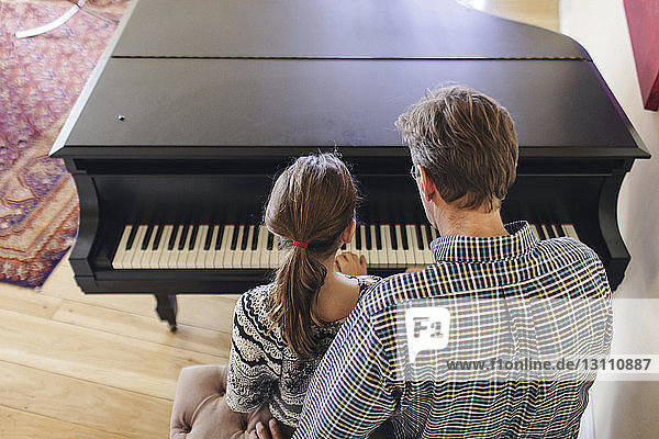 Rear view of father assisting daughter in playing piano while sitting at home