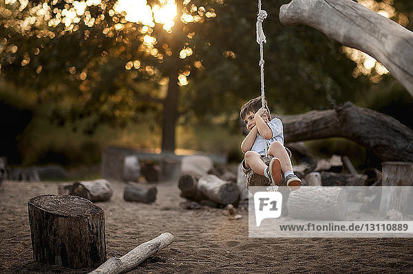 Playful boy swinging on rope swing at park