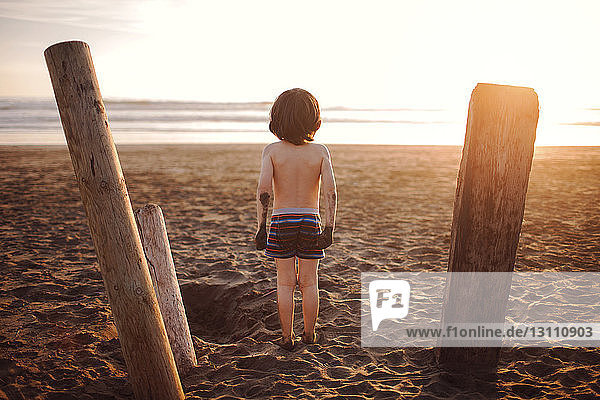 Rückansicht eines Jungen ohne Hemd  der im Sommer am Strand steht Rückansicht eines Jungen ohne Hemd, der im Sommer am Strand steht