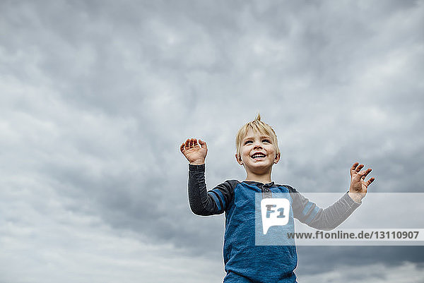 Low angle view of cheerful boy standing against cloudy sky