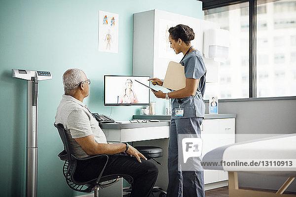 Ärztin diskutiert mit Kollegin in Konferenzschaltung  während der Patient in der Klinik sitzt