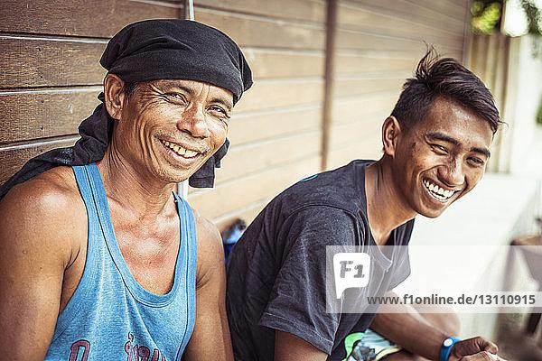 Porträt eines glücklichen Mannes mit Sohn an Holzwand sitzend