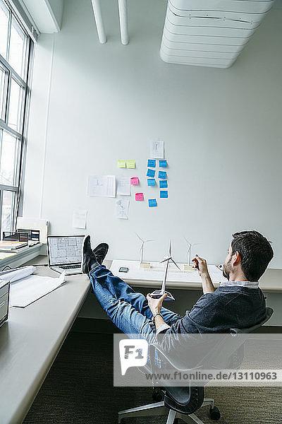 Seitenansicht eines Geschäftsmannes  der ein Windturbinenmodell hält  während er im Büro sitzt