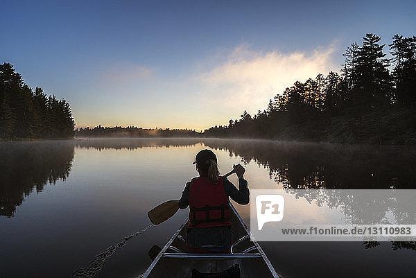 Rückansicht einer Frau  die bei Sonnenuntergang in einem Boot auf einem ruhigen See reist