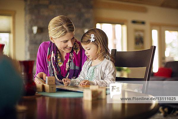 Mutter unterrichtet Tochter zu Hause auf dem Tisch