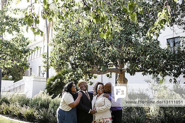 Glückliche Familie steht bei Pflanzen im Park