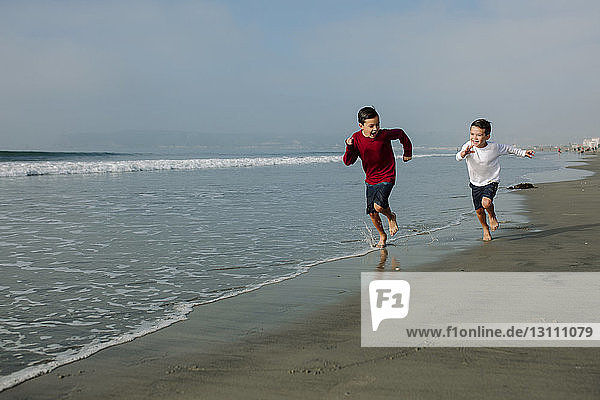 Full length of playful brothers running on shore at beach