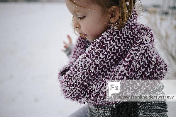 Seitenansicht eines süßen Mädchens mit Schal auf schneebedecktem Feld