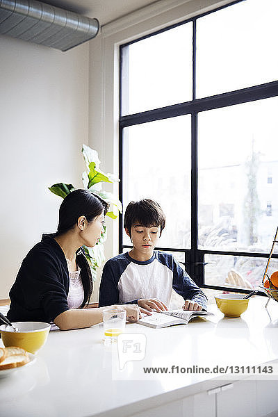 Mother teaching son on table in brightly lit home