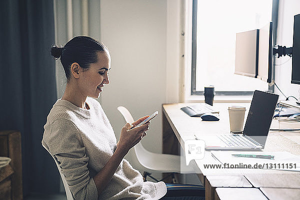 Businesswoman using smart phone while sitting at desk in office