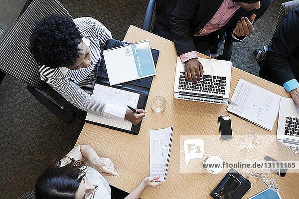 Draufsicht auf die Geschäftsleute am Schreibtisch während der Besprechung