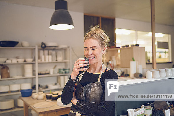 Smiling woman having drink while standing at workshop