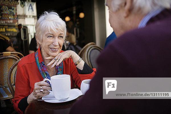Glückliche ältere Frau hält Kaffeetasse in der Hand  während sie mit einem Mann im Straßencafé sitzt