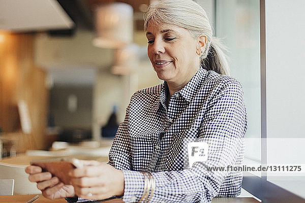 Businesswoman using mobile phone while sitting in cafeteria at office