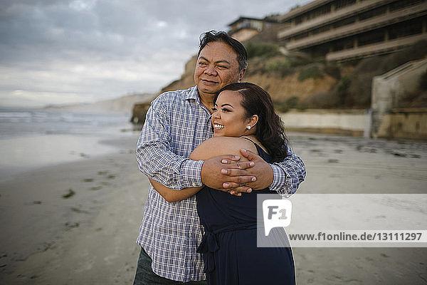 Glückliche Frau umarmt Vater  während sie am Strand gegen den Himmel steht